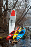 Colorful fiberglass kayaks lying on the rocky shore Stock Photos