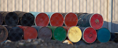 Colorful Fifty Gallon Drums. Colorful fifty gallon metal drums seen on end with one row stacked on the other against a metal building.  Drums are painted black Royalty Free Stock Photo