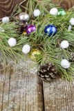 Colorful fir tree toys, pine cones, coniferous branches on Woode Stock Image