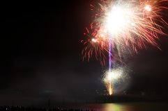 Colorful firework popping and lighting up the dark sky royalty free stock photography