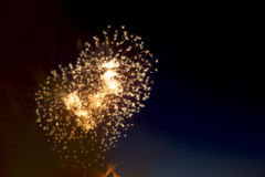 Colorful fireworks over dark sky, displayed during a celebration. Beautiful colorful holiday fireworks on the black sky background,  long exposure Royalty Free Stock Images