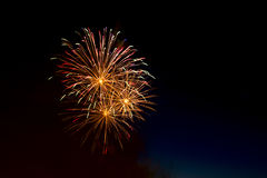 Colorful fireworks over dark sky, displayed during a celebration. Beautiful colorful holiday fireworks on the black sky background,  long exposure Royalty Free Stock Photo