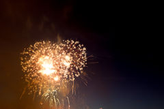 Colorful fireworks over dark sky, displayed during a celebration. Beautiful colorful holiday fireworks on the black sky background,  long exposure Stock Image