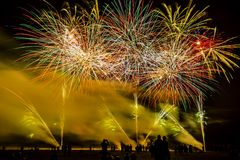 Colorful fireworks over night sky. Colorful fireworks of various colors over night sky with spectators Royalty Free Stock Photo