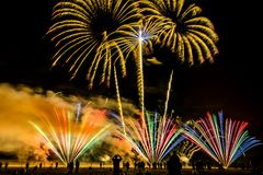 Colorful fireworks over night sky. Colorful fireworks of various colors over night sky with spectators Stock Photography