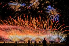 Colorful fireworks over night sky. Colorful fireworks of various colors over night sky with spectators Stock Image