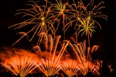 Colorful fireworks over night sky. Colorful fireworks of various colors over night sky with spectators Stock Images