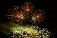 Colorful fireworks over night sky. Colorful fireworks of various colors over night sky with spectators Royalty Free Stock Photos