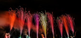 Colorful fireworks over night sky. Colorful fireworks of various colors over night sky with spectators Stock Photos