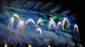 Colorful fireworks over night sky. Colorful fireworks of various colors over night sky with spectators Stock Photo