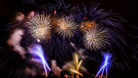 Colorful fireworks over night sky. Colorful fireworks of various colors over night sky with spectators Royalty Free Stock Images