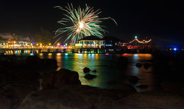 Colorful fireworks at pier in Sihanoukville,. Cambodia at night with reflection in the water and silhouettes of stones at foreground Royalty Free Stock Photography