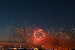 Colorful fireworks reflect from water, beautiful bridge scenery Royalty Free Stock Image