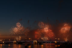 Colorful fireworks reflect from water, beautiful bridge scenery Royalty Free Stock Photos