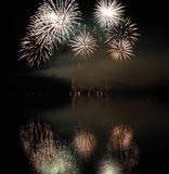 Colorful fireworks with reflection on lake. Royalty Free Stock Photos