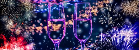 Colorful fireworks and two glasses of fizz champagne with bubbles close-up on the falling snow background royalty free stock images