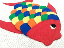 Children's chore, cloth fish. Colorful fish made for children. This is a chore that is done at school with pieces of colored cloth. The fabric is glued onto stock images