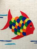 Children's chore, cloth fish. Colorful fish made for children. This is a chore that is done at school with pieces of colored cloth. The fabric is glued onto stock image