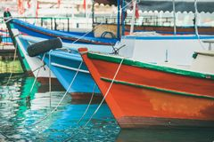 Colorful fishermens boats in small Mediterranean town. Colorful fishermens boats in water near the shore in harbour of old Mediterranean town Stock Photography