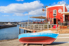 Colorful fishing boat in front of red restaurant building Royalty Free Stock Photos