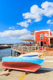 Colorful fishing boat in front of red restaurant building Royalty Free Stock Image