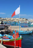 Colorful fishing boat with Maltese flag in Marsaxlokk, Malta. Colorful traditional fishing boat with Maltese flag in Marsaxlokk, Malta, a fishers village Stock Photos