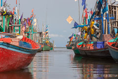 Colorful fishing boats floating along a canal Stock Image