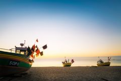 Colorful fishing cutters. Sopot, Poland, June 11, 2017: Sun just rises over colorful fishing cutters on sandy Sopot beach. Baltic sea, Pomerania. Poland stock photos