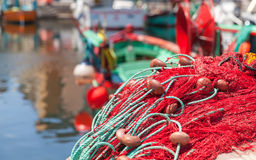 Colorful fishing net laying on a pier. Closeup photo with selective focus and blurred port background royalty free stock images