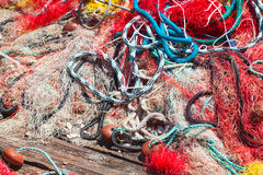 Colorful fishing net laying on wooden pier Stock Photography
