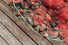 Colorful fishing net laying on wooden pier Royalty Free Stock Images