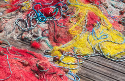 Colorful fishing nets lay on wooden pier Royalty Free Stock Images