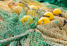 Colorful fishing ropes and floats. Colorful nets, coil of ropes and yellow floats used by fishermen for deep sea fishing stock image