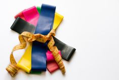 Colorful fitness gums tied up with meter tape isolated on white background. Sport concept - elastic expanders of different colors royalty free stock images