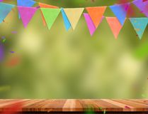 Colorful flag banner and confetti on wood table with blur green. Tree bokeh background, Template mock up for montage of product.party garland holiday backdrop stock photos