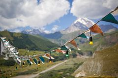 Colorful flags, garlands of light bulbs and a hammock on the background of a mountain valley overlooking the top of Kazbegi. stock images
