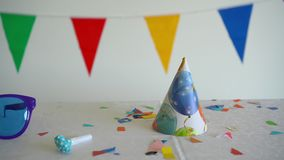 Colorful flags glasses confetti. Table after children party. Gimbal movement. Colorful flags glasses hat and confetti. Room table after children birthday party stock footage