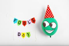 Colorful flags with phrase. `Fool`s day` and funny balloon on light background. 1st April composition Royalty Free Stock Photo