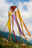 Colorful prayer flags. Hanging from pole with mountains and cloudscape background Stock Images