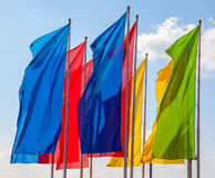 Colorful flags waving over blue sky Royalty Free Stock Image