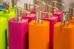 Colorful flasks. Closeup of many colorful plastic bottled flasks orange pink and green colors standing in raw close to each other with spray top, horizontal stock image