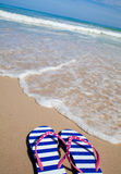 Colorful flip-flop sandals on sea beach Stock Photo