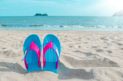 Colorful flip flops on beach against sunny sky. Summer vacation concept Stock Image