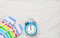 Colorful flip flops and classic alarm clock Stock Images