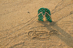 Colorful flip flops and heart shape on white sand beach Royalty Free Stock Photos