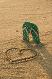Colorful flip flops and heart shape on white sand beach Royalty Free Stock Photography