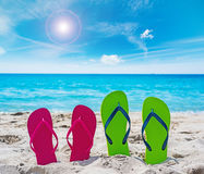 Colorful flip flops on the sand Stock Images