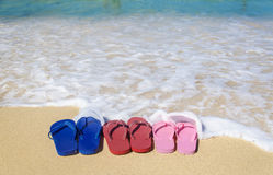 Colorful flip flops on the sandy beach Stock Photo