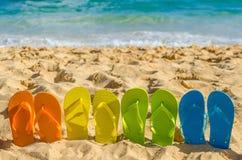Colorful flip flops on the sandy beach Stock Photos