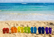 Colorful flip flops on the sandy beach Stock Images